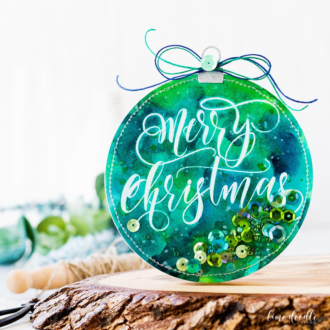 Watercolored Shaker Ornament by Debby Hughes. Find out more about this Christmas card by clicking on the following link: http://limedoodledesign.com/2016/12/watercolored-shaker-ornament/
