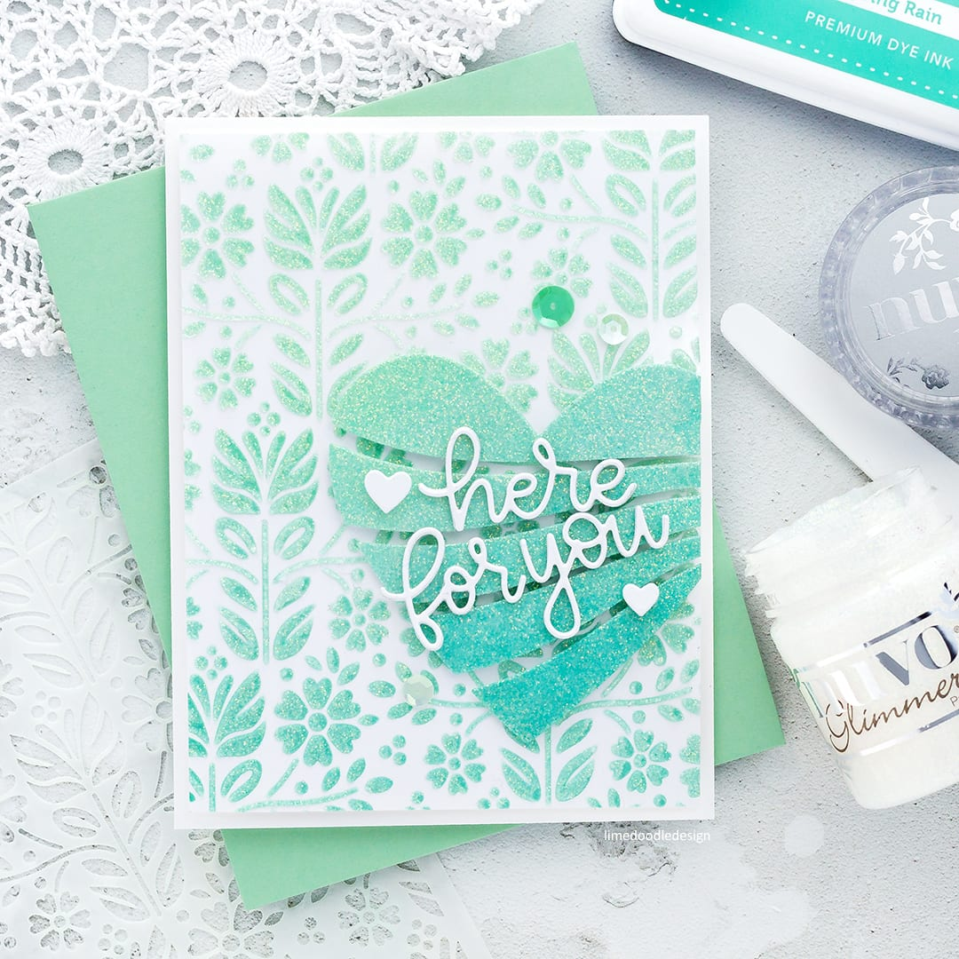 Creating lots of sparkle with the new Folk Dance Stencil and Streaming Heart die from Simon Says Stamp and Nuvo Glimmer Paste. Here For You handmade card by Debby Hughes. Find out more here: http://limedoodledesign.com/2018/01/adding-sparkle-simon-says-stamp-new-release/