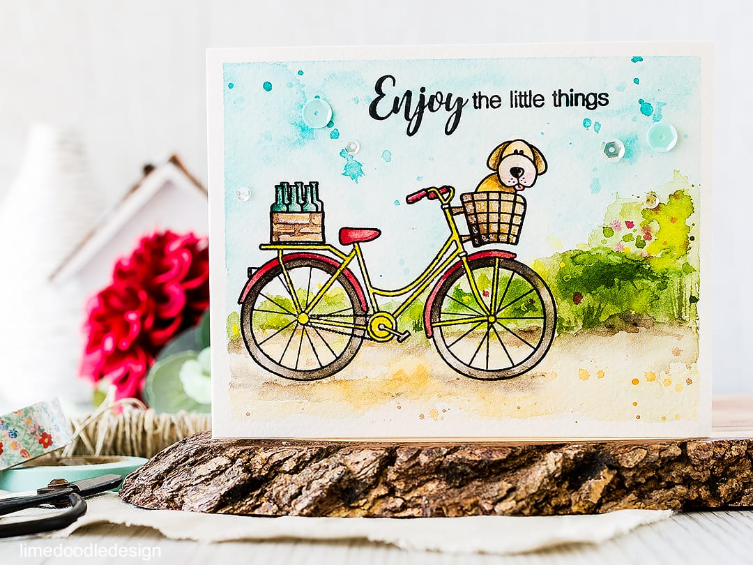 A simple watercolored card of a bike on a country lane including a pup in the basket! Find out more by clicking on the following link: https://limedoodledesign.com/2016/04/watercolored-country-lane/