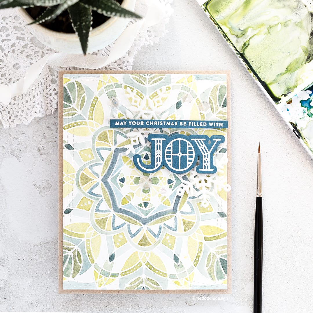 Mosaic/spotlight watercolouring a soft and elegant background for this handmade Christmas card by Debby Hughes using the Centre Cut Kaleidoscope Bakcground and Stained Glass Greetings set from Simon Says Stamp. Find out more here: https://limedoodledesign.com/2017/11/mosaic-watercolour/