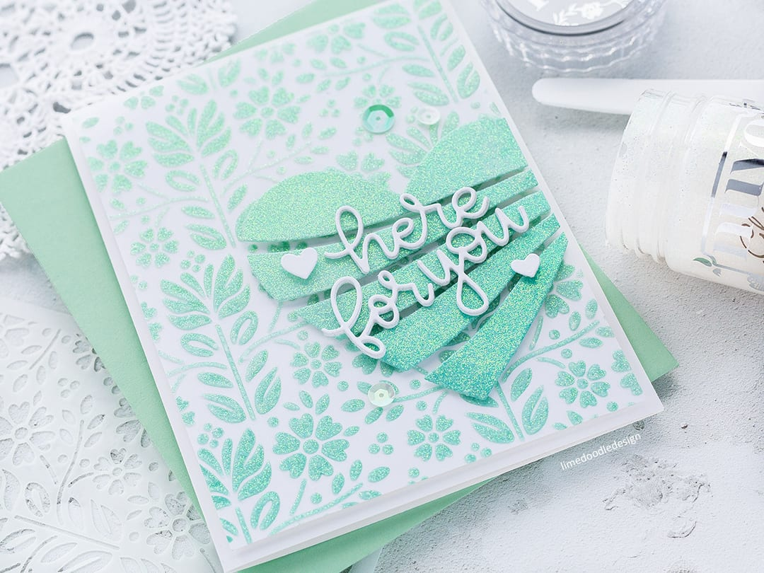 Creating lots of sparkle with the new Folk Dance Stencil and Streaming Heart die from Simon Says Stamp and Nuvo Glimmer Paste. Here For You handmade card by Debby Hughes. Find out more here: https://limedoodledesign.com/2018/01/adding-sparkle-simon-says-stamp-new-release/