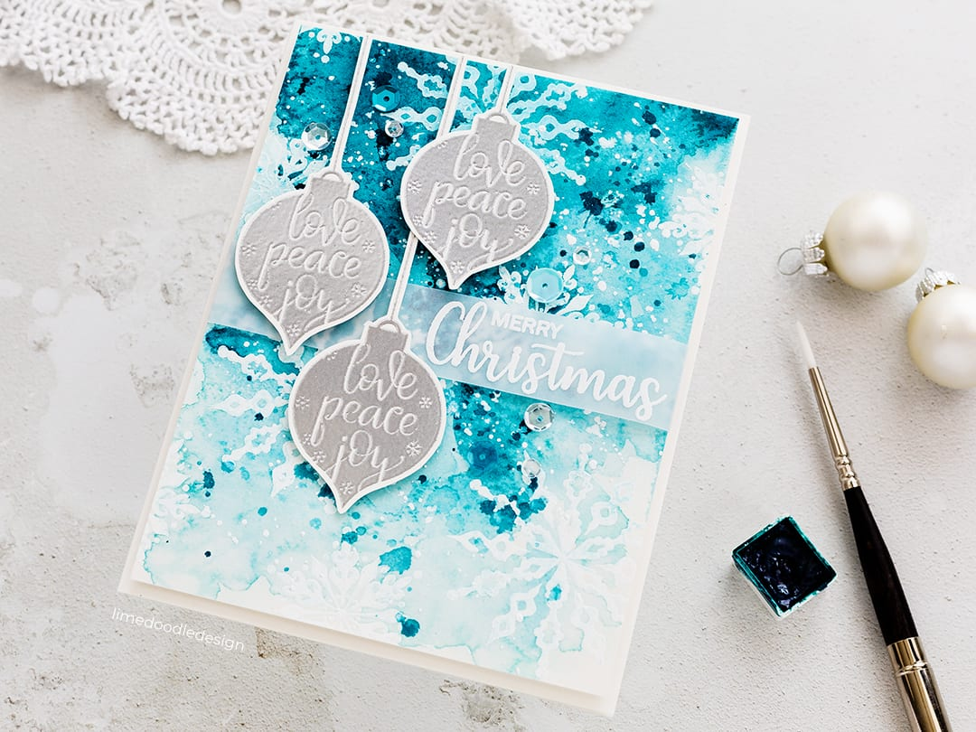Heat embossed snowflakes resisting an intense blue watercoloured background with silver ornaments. Handmade card by Debby Hughes using the GinaK STAMPtember set. Find out more here: https://limedoodledesign.com/2018/09/ginak-stamptember/