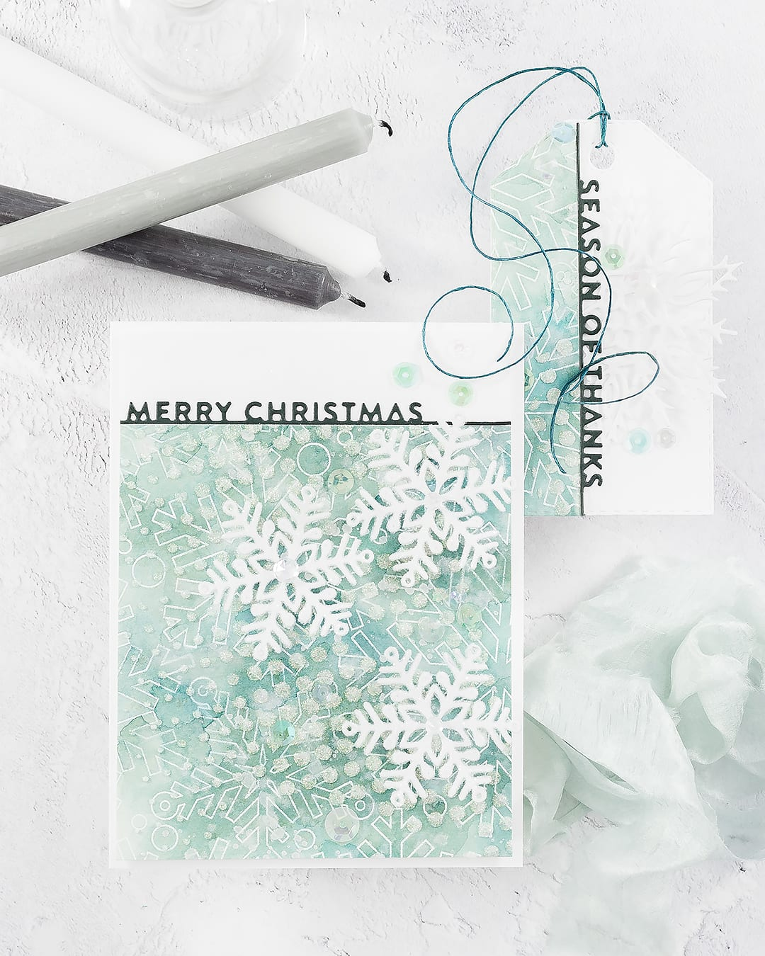 Softly watercoloured, layered snowflake background handmade Christmas card and tag by Debby Hughes. Find out more here: https://limedoodledesign.com/2018/11/video-watercoloured-layered-snowflake-background/