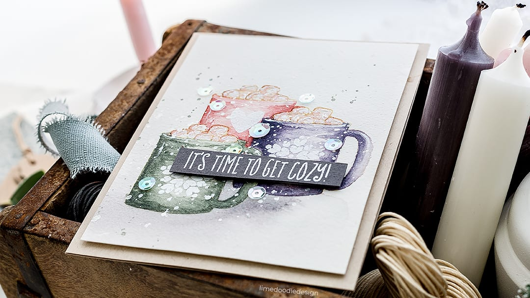 Video tutorial watercolouring cosy cocoa cups with marshmallows. Handmade card by Debby Hughes using supplies from Wplus9 and Daniel Smith. Find out more here: https://limedoodledesign.com/2018/11/video-watercoloured-cosy-cocoa-mugs/