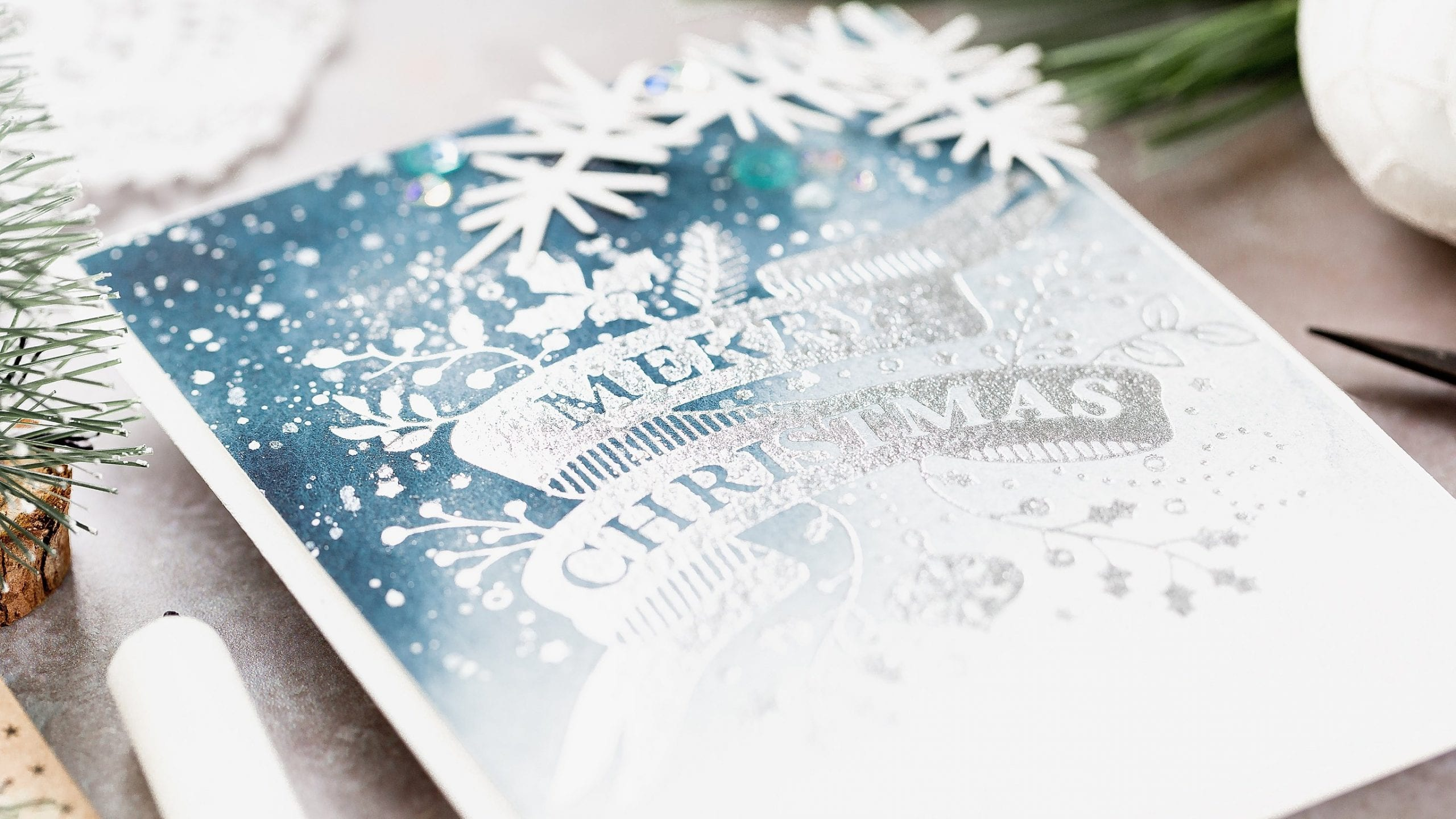 Silver foiled deep blue watercoloured Christmas handmade card by Debby Hughes using supplies from Spellbinders. Find out more here: https://limedoodledesign.com/2019/08/video-foiled-watercolour-christmas-card/