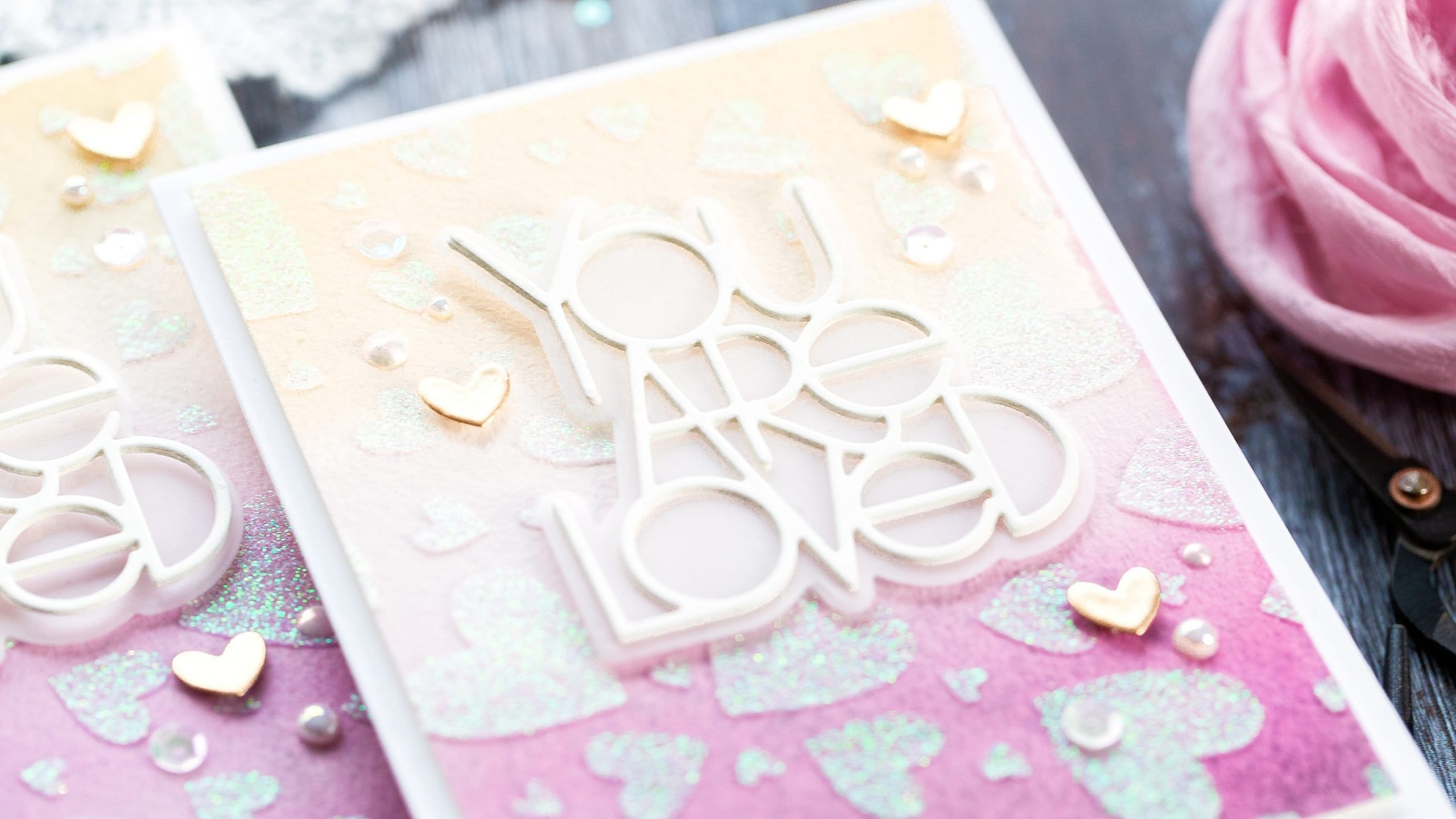 Simple watercolour gradient wash as a backdrop to glittery hearts and a 'You Are Loved' die cut sentiment. Handmade valentine's card by Debby Hughes using supplies from Simon Says Stamp.